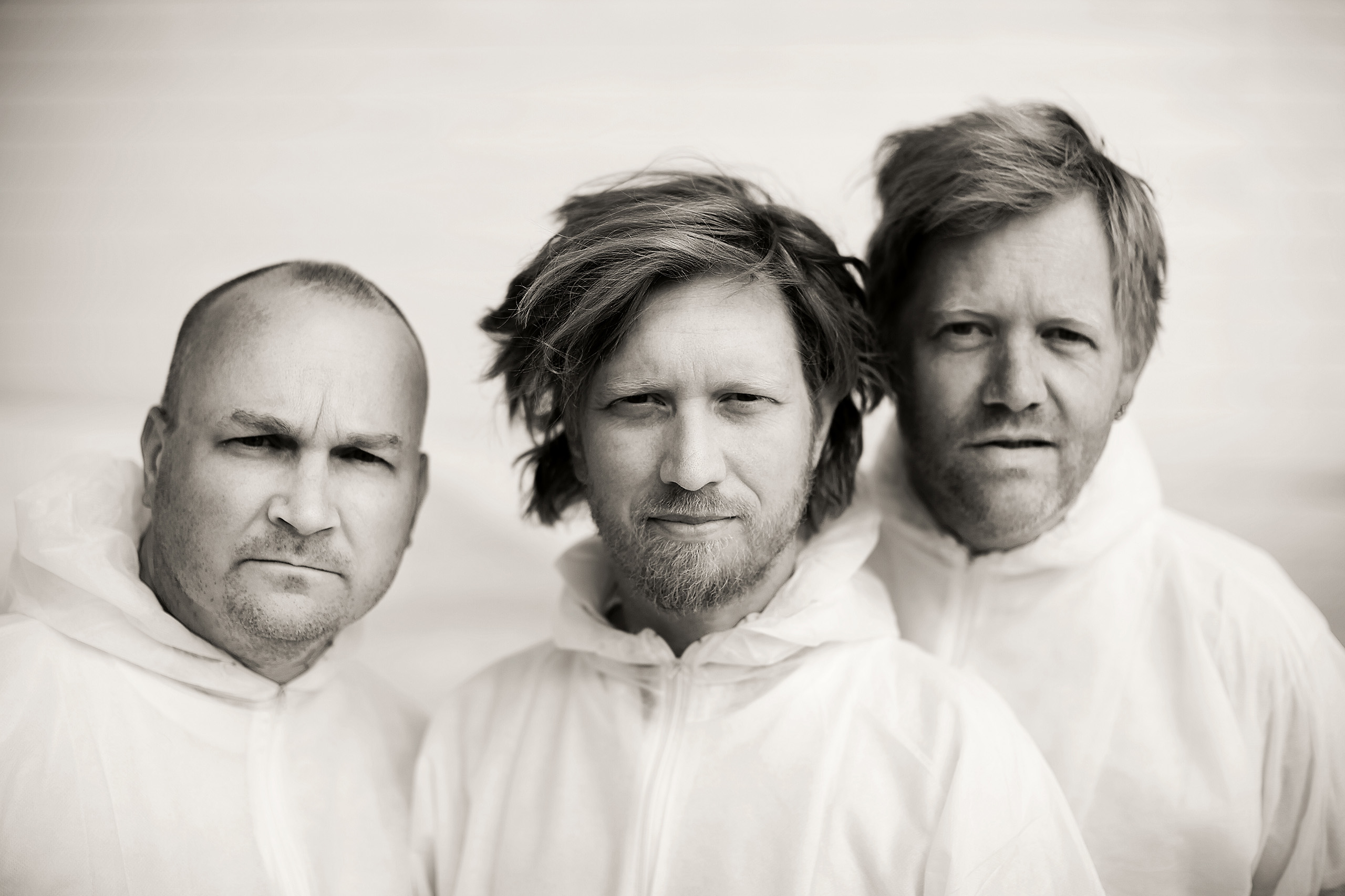 Photo of the Helge Lien Trio musicians: Frode Berg, Helge Lien and Per Oddvar Johansen in white overalls. Black and white with a tint of sepia.